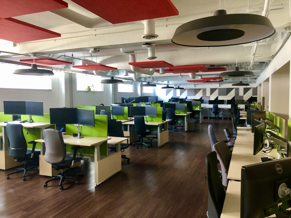 espace de travail rempli de postes de travail et de panneaux muraux et de plafond colorés