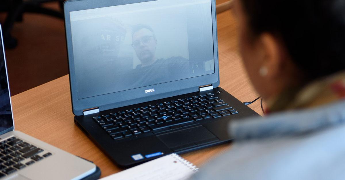 Jeune femme parlant à un collègue via son ordinateur portable