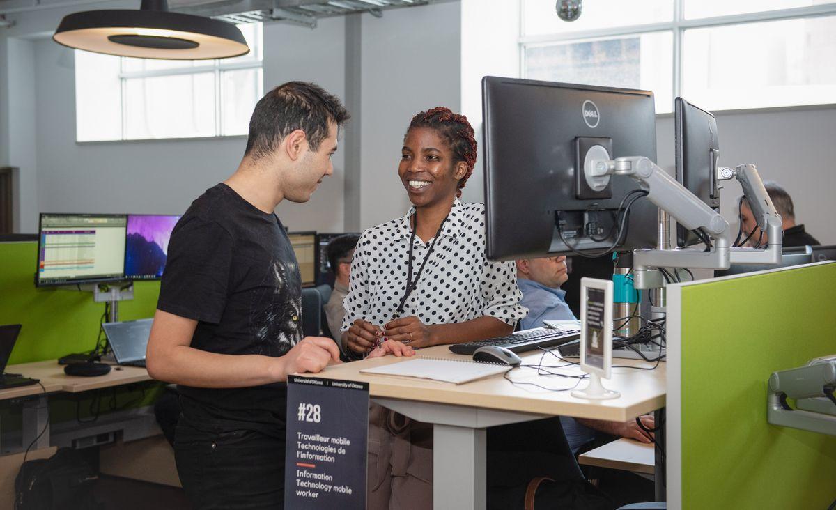 Un homme et une femme sont debouts et discutent devant un bureau de travail surélevé.