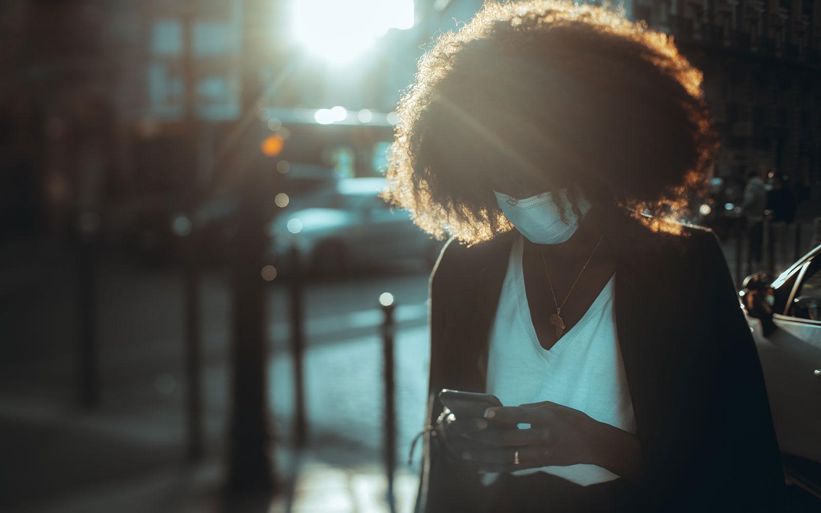 Une silhouette d'une femme africaine portant un masque facial et à l'aide d'un smartphone sur une rue de la ville par une soirée ensoleillée