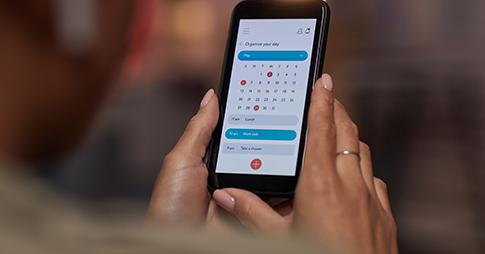 mains féminines tenant un smartphone avec calendrier électronique affiché