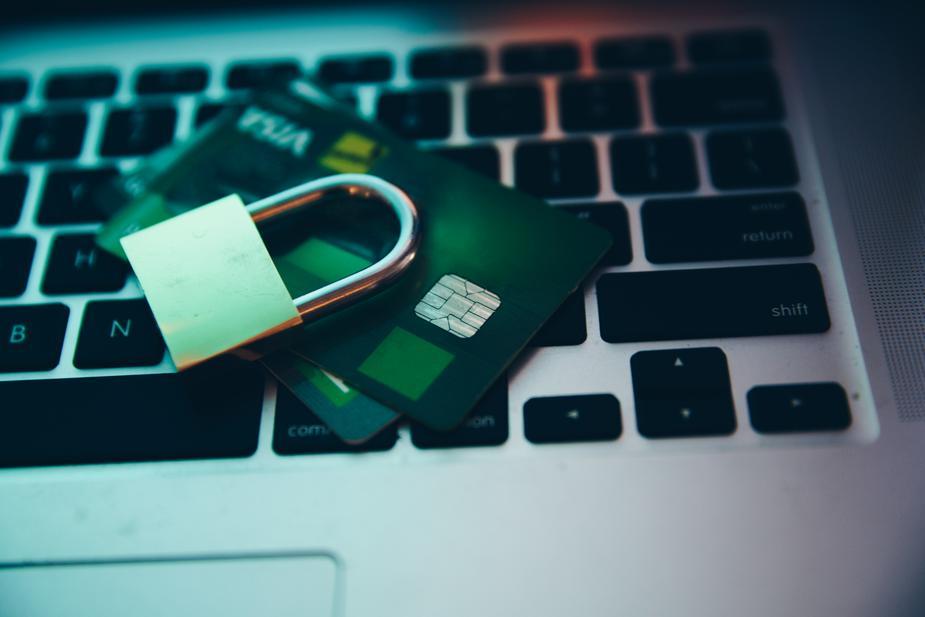 des cartes de crédit et un cadenas empilé sur un clavier d'ordinateur portable