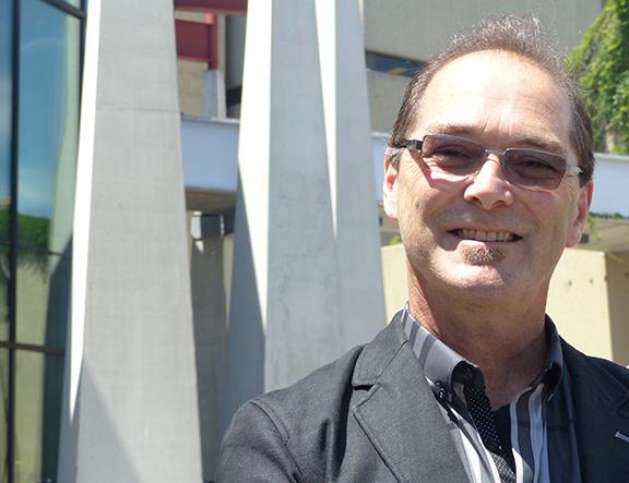 Homme photographié depuis les épaules en veste d'affaires et lunettes de soleil face à la caméra et souriant, la construction de colonnes en arrière-plan