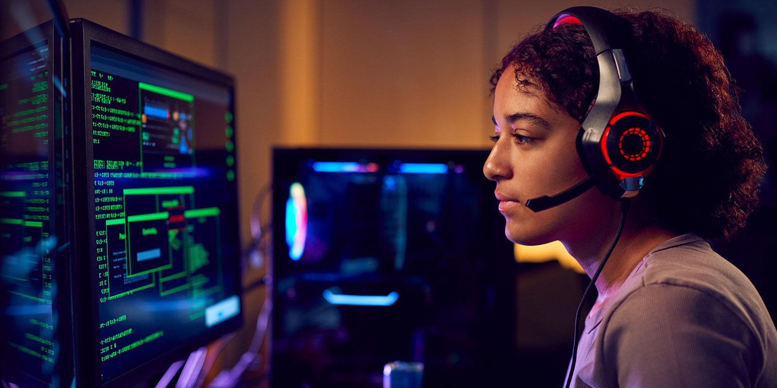 Femme avec casque assis sur deux moniteurs d'ordinateur et en tapant sur le clavier, des moniteurs supplémentaires en arrière-plan