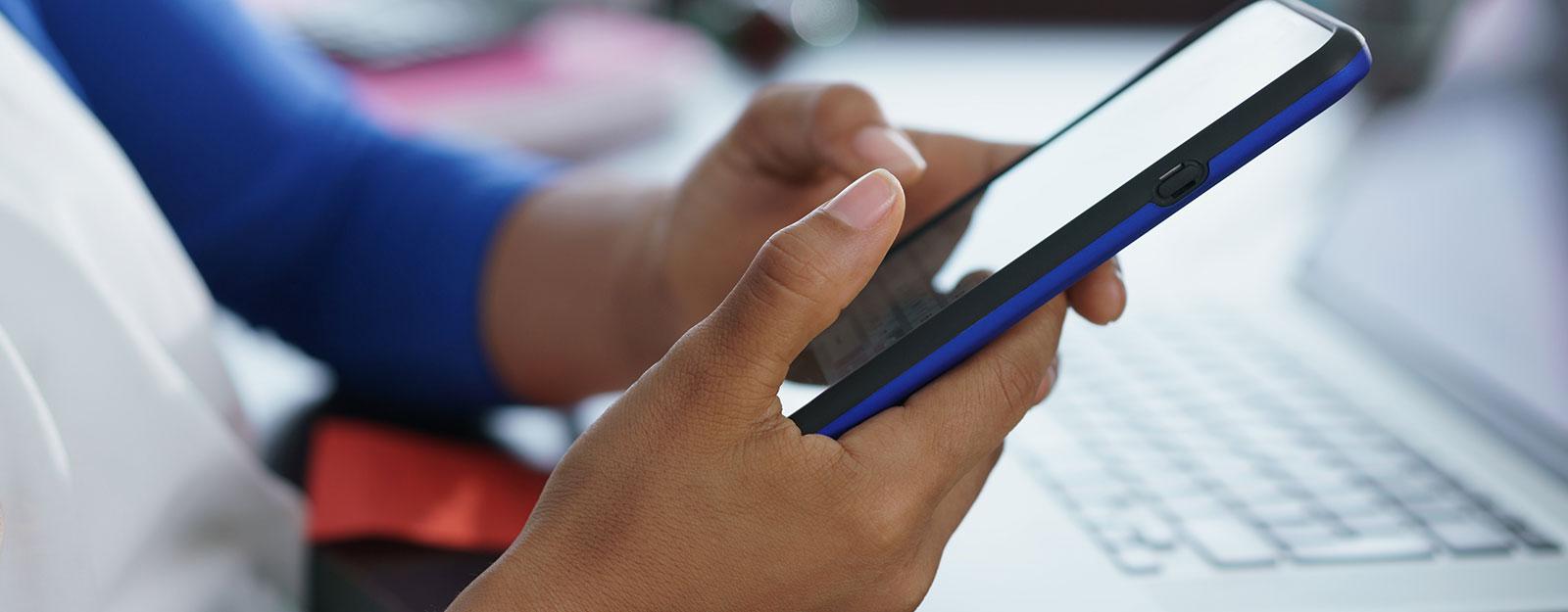 jeunes femmes tapant sur un smartphone bleu et noir avec ordinateur portable et cahiers en arrière-plan