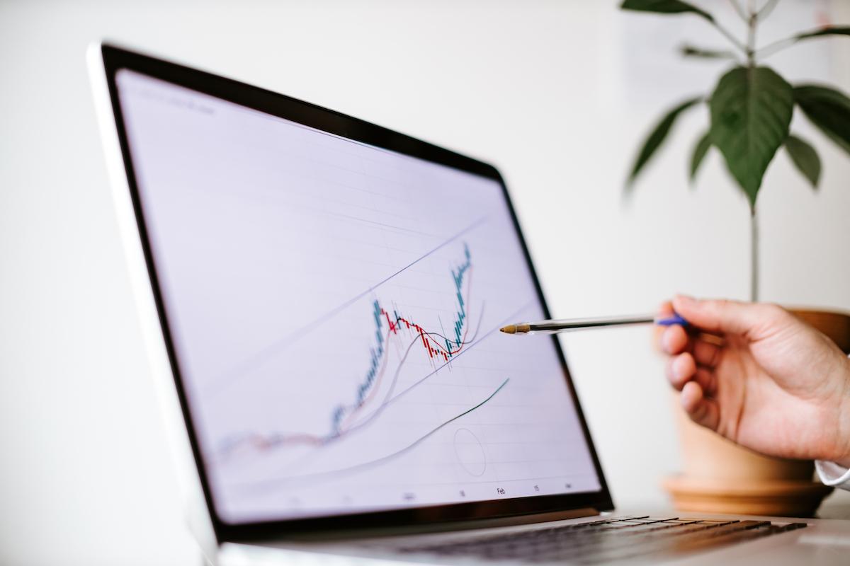 ordinateur portable affichant des graphiques avec une main tenant un stylo pointant sur une section du graphique
