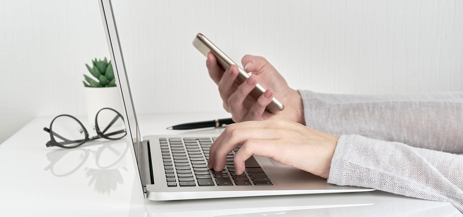75/5000 Main féminine tapant sur un ordinateur portable tout en tenant un smartphone dans son autre main